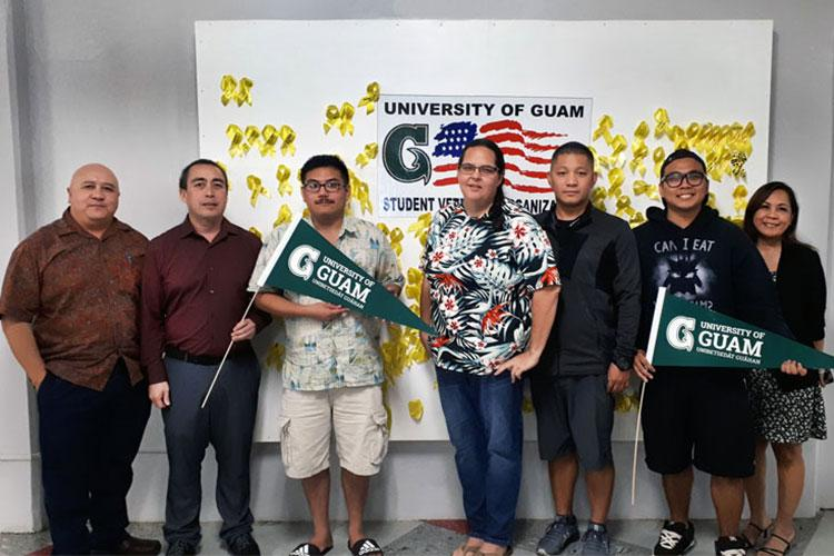 Veteran students at the University of Guam in February 2020 stand in the UOG Student Center by a board of yellow ribbons that each commemorate a UOG veteran. (From left) Lawrence Camacho, dean of Enrollment Management and Student Success; Dan Camacho; Jan Fontbuena; Amy Jackson; Mark Mantanona; Anthony Mamaligsa; and Arline Leon Guerrero, Veterans Resource Center academic advisor.