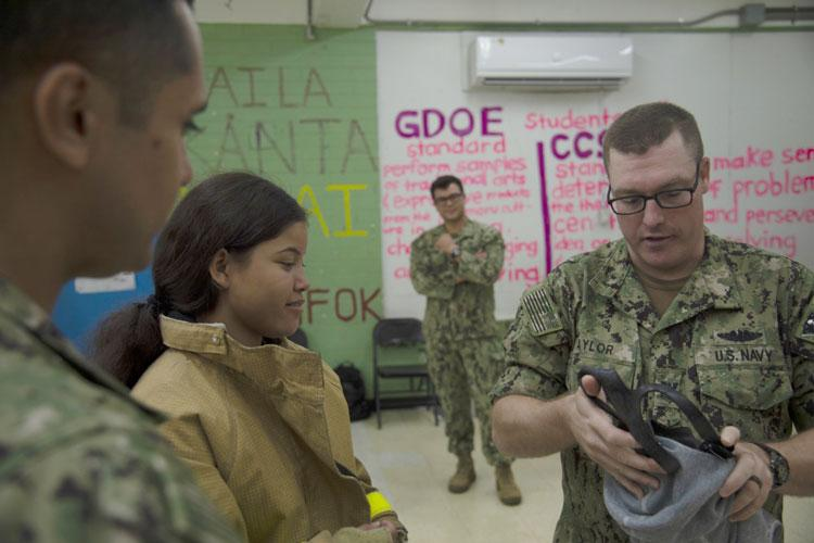 INARAJAN, Guam (Feb. 21, 2020) — Chief Yeoman Eddie Aviles, from East Los Angeles, Calif., left, and Machinist's Mate (Auxiliary) 1st Class Jerid Taylor, from Abilene, TX, right, both assigned to Commander, Submarine Squadron 15 (CSS 15), explains to an Inarajan Middle School student how to properly don an emergency air breathing apparatus during a hands-on demonstration at Inarajan Middle School Feb. 21. (U.S. Navy photo by Mass Communication Specialist 2nd Class Destinyy Reed/Released)