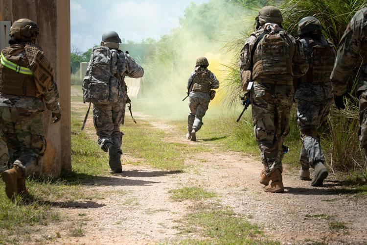 """Students in a Tactical Combat Casualty Care class run to secure a location during the """"care under fire"""" portion of their training, May 13, 2020 at Andersen Air Force Base, Guam. TCCC puts students in a simulated combat zone, where they will learn to operate under pressure using the techniques they learned in the classroom. (U.S. Air Force photo by Senior Airman Zachary Heal)"""