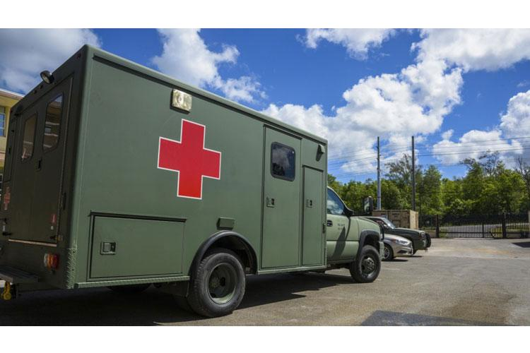 A military emergancy medical transport vehicle, assigned to Expeditionary Medical Facility (EMF) Camp Pendleton, sits in the parking lot of the EMF constructed on Naval Base Guam's Santa Rita Compound. The EMF will provide expanded medical capabilities in support of DoD's COVID-19 response and will enable forces to be postured to support Guam and the region if a Defense Support of Civil Authorities mission is requested. (U.S. Navy photo by Mass Communication Specialist 3rd Class MacAdam Kane Weissman)