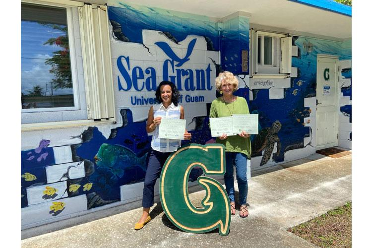 (From left) University of Guam faculty Sarah Lemer, assistant professor of marine invertebrate genomics, and Laurie Raymundo, interim director of the UOG Marine Laboratory and professor of marine biology, hold certificates of grants they were awarded from UOG Sea Grant to continue critical research on coral restoration and reef recovery on Guam. (Photos courtesy of the University of Guam)