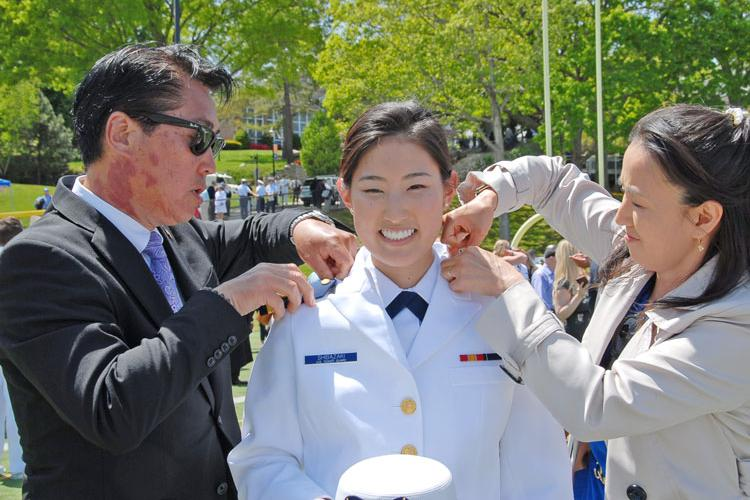 Coast Guard Ensign Sasha Shibazaki gets her new rank pinned on by her parents Bobby and Nisako May 22 after graduating from the Coast Guard Academy. Shibazaki is a 2014 alumnus of M.C. Perry High School, Marine Corps Air Station Iwakuni, Japan. (Courtesy Photo)