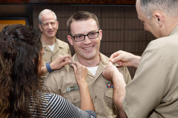 SAN DIEGO (April 1, 2019) Command Master Chief Loren Rucker, command master chief of Navy Medicine West, pins first class insignia on Hospital Corpsman 1st Class David Taylor, with help from Taylor's wife. Rear Adm. Paul Pearigen meritoriously advanced Taylor during an all-hands call at Navy Medicine West headquarters at Naval Base San Diego. (U.S. Navy photo by chief Mass Communication Specialist Michael O'Day/Released)