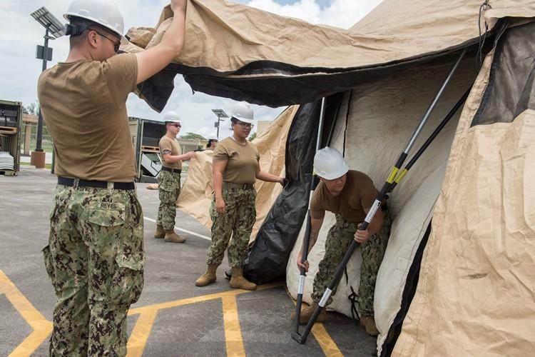 Reserve Sailors assigned to Navy Expeditionary Forces Command Pacific (NEFCPAC), adjust the legs of a tent in preparation for integrated training during an integrated training evolution. Active duty and reserve components assigned to NEFCPAC, work together to execute operational command and control of assigned and attached Navy Expeditionary Combat Forces in the U.S. 7th Fleet area of operations and serve as the core Navy battle staff for crisis response and major combat operations.