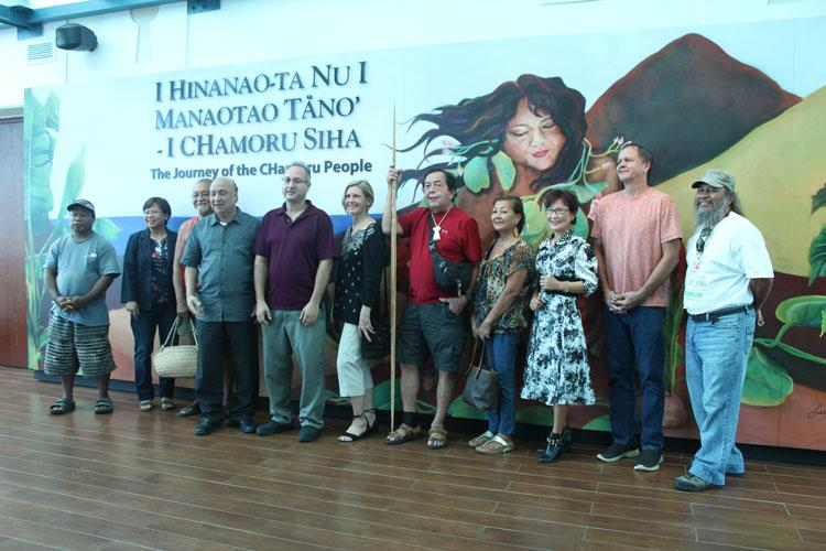 Local artists who participated in the production of artwork for the permanent exhibition stand in front of the title mural.