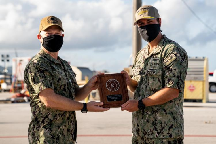"""SANTA RITA, Guam (Feb. 26, 2021) Capt. Bret Grabbe, commodore of Commander, Submarine Squadron 15, presents the Battle """"E"""" award to Cmdr. Michael McGuire, captain of the Los Angeles-class fast-attack submarine USS Key West (SSN 722). Key West is one of multiple submarine commands assigned to CSS-15 out of Polaris Point, Naval Base Guam. (U.S. Navy photo by Mass Communication Specialist 2nd Class Kelsey J. Hockenberger)"""