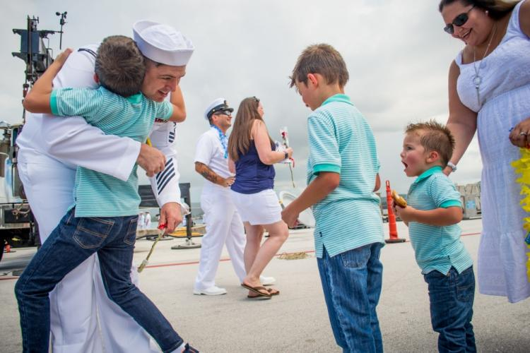 SANTA RITA, Guam (Aug. 18, 2019) - Machinist Mate (Nuclear) 1st Class Nicholas Miller, assigned to the Los Angeles-class fast attack submarine USS Oklahoma City (SSN 723), from Ontario, Calif., greets his family during a homecoming celebration following a four month deployment. Oklahoma City is one of four forward-deployed submarines assigned to Commander, Submarine Squadron Fifteen out of Apra Harbor, Guam. (U.S. Navy photo by Mass Communication Specialist 2nd Class Kelsey J. Hockenberger)