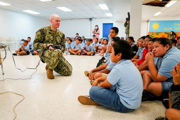 Electricians Mate (Nuclear) 1st Class Joe Severin, assigned to the Performance Monitoring Team at Commander, Submarine Squadron Fifteen, from Seal Beach, Calif., teaches students about a thermal imager, used for electrical maintenance, during a career day at Marcial A. Sablan Elementary School. (U.S. Navy photo by Mass Communication Specialist 2nd Class Kelsey J. Hockenberger)