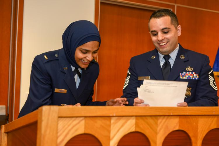 Second Lt. Saleha Jabeen, chaplain candidate, and Master Sgt. Alexander James, recruiter, sign recruitment paperwork after Jabeen's commissioning ceremony Dec. 18, 2019, at the Catholic Theological Union in Chicago. Jabeen is scheduled to continue training and be assigned to a unit once she has completed all initial training requirements. (U.S. Air Force photo by Tech. Sgt. Armando A. Schwier-Morales)