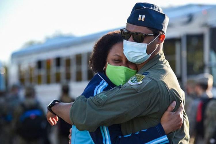 An Airman gives his mother a hug goodbye before boarding a bus to leave for deployment at Joint Base Langley-Eustis, Virginia, Nov. 5, 2020. A contingent of 94th Fighter Squadron Airmen and F-22 Raptors assigned to the 1st Fighter Wing, deployed to Andersen Air Force Base, Guam, to conduct missions in the Western Pacific with allies and joint partners. (U.S. Air Force photo by Senior Airman Alexandra Singer)