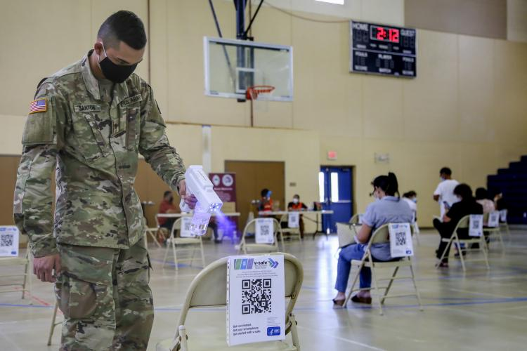 """Pvt. 1st Class Charles Santos of the Guam National Guard sanitizes the observation area at the Okkodo High School COVID-19 vaccination site in Dededo on Jan. 13. """"I'm here for anything I can do to make a difference,"""" said Santos."""