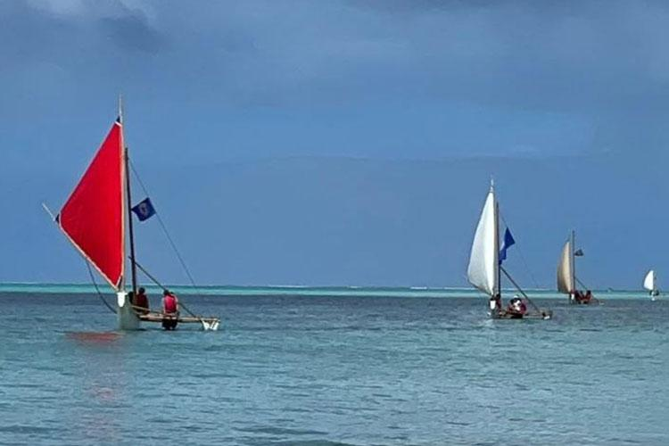 """Four 500 Sails canoes eagerly awaiting their new yellow-sailed sister, """"Auntie Oba""""."""