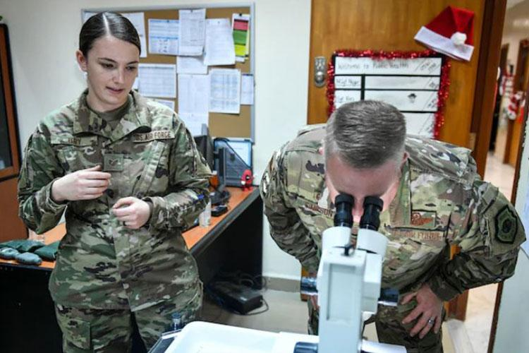Staff Sgt. Shannon Ury, 386th Air Expeditionary Wing public health technician, looks on as Col. Rod Simpson, 386th Air Expeditionary Wing commander, sorts between male and female mosquito specimens during a visit to the medical group at Ali Salem Air Base, Kuwait, Dec. 12, 2019. The female mosquitoes are separated and sent to a location within the United States for entomologists to examine for viruses or diseases. (U.S. Air Force photo by Staff Sgt. Mozer O. Da Cunha)