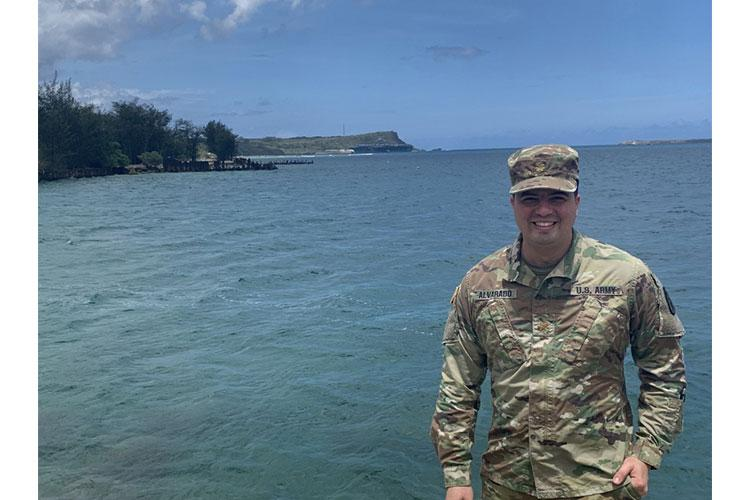 Army Maj. (Dr.) Gadiel Alvarado, infectious diseases physician, poses for a photo in Guam with the USS Theodore Roosevelt (CVN 71) in the background April 18, 2020. Alvarado served as the infectious disease expert for the COVID-19 Public Health Task Force from April 12-22. The team, consisting of five Army officers, was there to perform a comprehensive and multidisciplinary review of processes, asses the current situation and help with mitigation plans surrounding the TR COVID-19 outbreak. (courtesy photo)