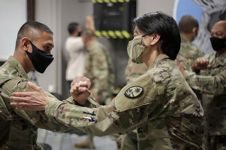 Amn. 1st Class Jacob Taisipic of the 254th Security Forces Squadron, Guam Air National Guard, left, receives encouragement from Maj. Gen. (GU) Esther Aguigui, adjutant general,  during a sendoff ceremony in Yigo on Dec. 28. Taisipic and a portion of his unit are bound for the CENTCOM area of operations.