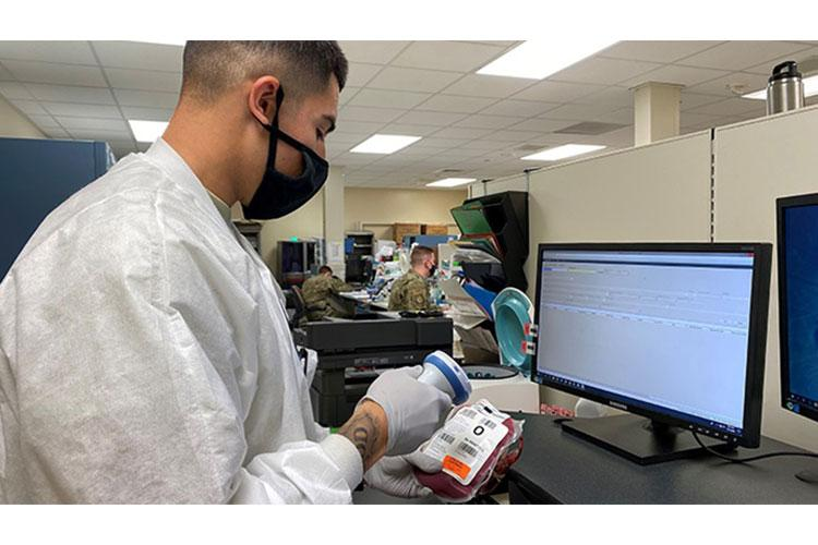 A1C Jakub Lopez, blood bank technician, scanning a unit of blood into MHS GENESIS inventory. MHS GENESIS serves as both an electronic health record and electronic blood management system. (Photo submitted by 60th Medical Group, David Grant USAF Medical Center)
