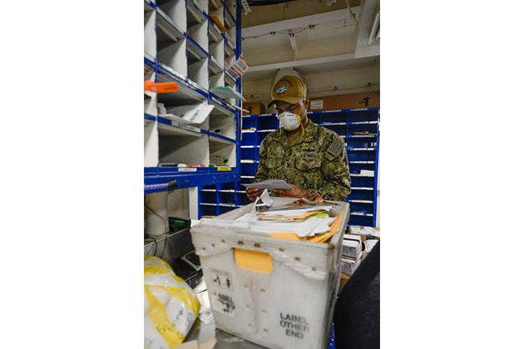 NAVAL BASE GUAM (MAY 8, 2020) – U.S. Navy Logistics Specialist 2nd Class Desmond Hall, from Stuttgart, Germany, organizes incoming mail in the mail room aboard the aircraft carrier USS Theodore Roosevelt (CVN 71) May 8, 2020. Theodore Roosevelt's COVID-negative crew returned from quarantine beginning on April 29 and is making preparations to return to sea to continue their scheduled deployment to the Indo-Pacific. (U.S. Navy photo by Mass Communication Specialist Seaman Erik Melgar)