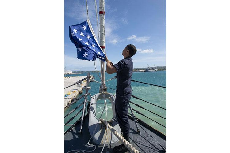 NAVAL BASE GUAM (Feb. 14, 2020) U.S. Navy Retail Services Specialist Seaman Jomar Jaquez, from North Bergen, N.J., raises the Union Jack flag aboard the Arleigh Burke-class guided-missile destroyer USS Kidd (DDG 100) Feb. 14, 2020. Kidd, part of the Theodore Roosevelt Carrier Strike Group, is in Guam for a port visit during their scheduled deployment to the Indo-Pacific. (U.S. Navy photo by Mass Communication Specialist 3rd Class Brandie Nuzzi)
