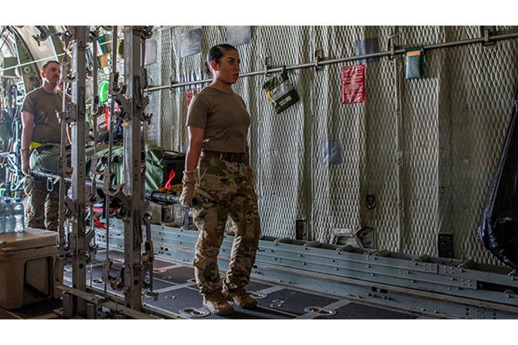 Air Force Senior Airman Vanessa Colindres, 379th Expeditionary Aeromedical Evacuation Squadron medical technician (right), helps load a litter of medical gear onto a C-130 Hercules aircraft to prepare for a combat aeromedical evacuation mission at Al Udeid Air Base, Qatar in August 2020. (Photo by Senior Airman Ashley Perdue, 379th Air Expeditionary Wing Public Affairs.)