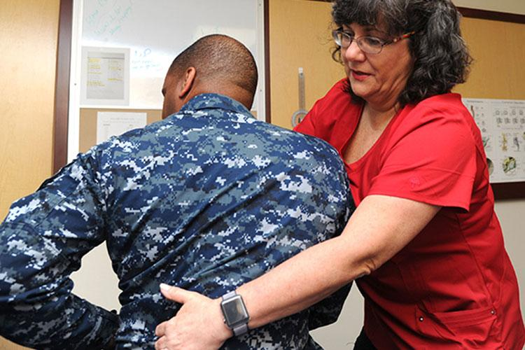 Debra Goolsby, a physical therapist at Naval Hospital Pensacola's Pain Clinic, works with a patient during a session. Goolsby uses a technique called Total Motion Release to help her patients reduce and eventually eliminate pain without using medications. (Photo by Jason Bortz.)