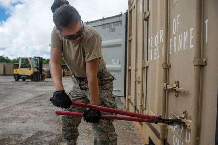 U.S. Air Force Airman 1st Class Valeria Pulido, a munitions inspection technician assigned to the 36th Munitions Squadron, breaks open a storage container seal after arriving to its final destination at Andersen Air Force Base, Guam, Nov. 15, 2020. The Navy and the Air Force continue to develop and maintain operational compatibility by completing munition transport operations while also ensuring combat readiness to both forces. (U.S. Air Force photo by Senior Airman Michael S. Murphy)