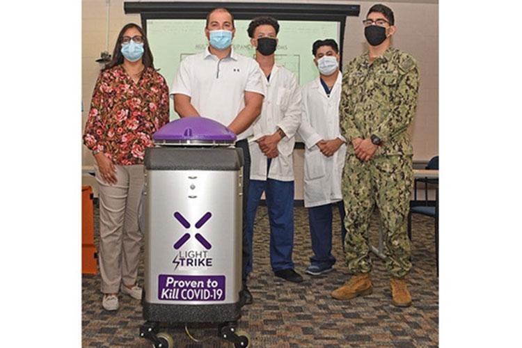 Teresa Turbyfill, hospital infection preventionist (left), poses with NHTP hospital corpsmen and a company representative, behind one of their new broad spectrum UV light robotic units. (Photo by David Marks, NHTP PAO.)