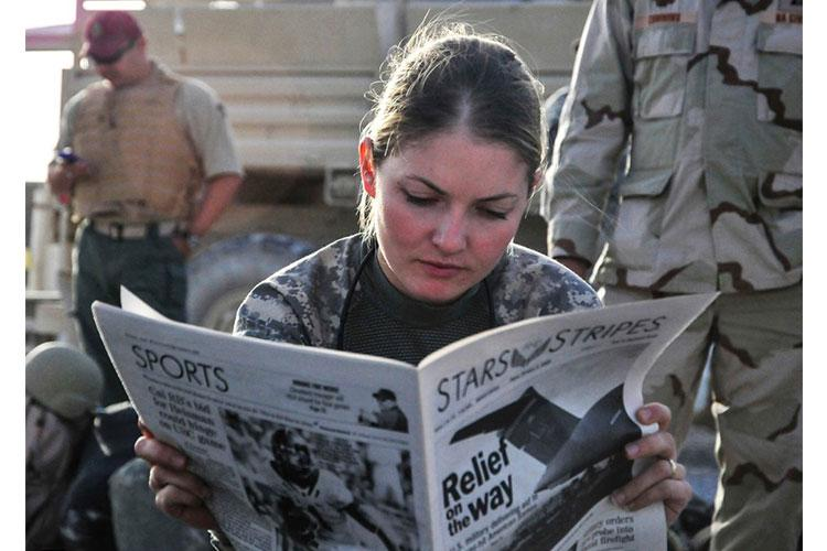 U.S. Army 1st Lt. Tracy Tyson, with 5th Brigade Combat Team, 2nd Infantry Division, reads the Stars and Stripes newspaper at Kandahar Airfield, Afghanistan, Oct. 5, 2009, while waiting for a flight to Forward Observation Base Wolverine. ERNESTO HERNANDEZ FONTE/U.S. NAVY