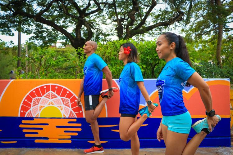 UGM Race Ambassadors Leo Tkel, Manami Iijima and Rhea Macaluso stretch at the new United Airlines Guam Marathon's Runners' Oasis in front of the Pacific Islands Club parking garage in Tumon before their run. The mural was designed and painted by local artists Austin Domingo and Kristine Leigh Bactad.