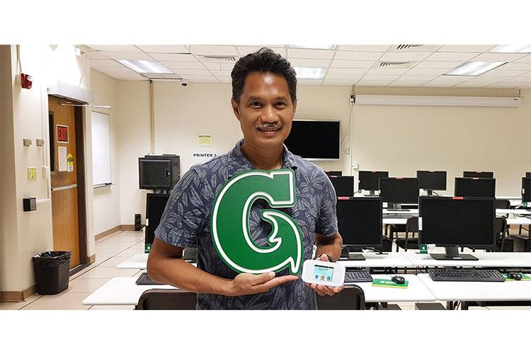 Manny Hechanova, Interim Chief Information Officer of the University of Guam, accepts a donation of 30 mobile hotspot devices and 4G LTE data from IT&E. UOG will distribute the devices to students. (Photo courtesy of University of Guam)