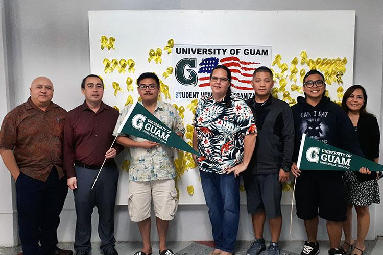 Veteran students at the University of Guam stand in the UOG Student Center by a board of yellow ribbons that each memorialize or commemorate a special veteran. (From left) Lawrence Camacho, dean of Enrollment Management and Student Success; Dan Camacho; Jan Fontbuena; Amy Jackson; Mark Mantanona; Anthony Mamaligsa; and Arline Leon Guerrero, Veterans Resource Center academic advisor. Photo courtesy of the University of Guam