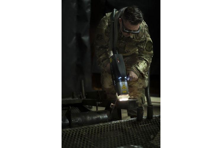 SSgt Brendan McCormick, 36th Maintenance Squadron Corrosion Control NCOIC, uses an ablative cleaning laser to remove rust from a stair lift, Feb. 27, 2019, Andersen Air Force Base, Guam. An ablative laser is a tool used to remove rust by emitting UV rays strong enough to vaporize rust and other materials such as paint and residue. (U.S. Air Force photo by Airman 1st Class Zachary Heal)