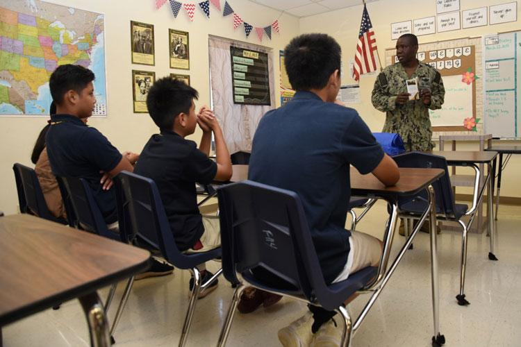 DEDEDO, Guam (March 22, 2019) Lt. Wilking Jean, command chaplain aboard USS Emory S. Land (AS 39), talks to students at Astumbo Middle School in Dededo, Guam, during a career day at the school. Several Sailors from Land attended the event to share information with the students about the various career oportunities the Navy offers.(U.S. Navy photo by Mass Communication Specialist 1st Class Jason Behnke/Released)
