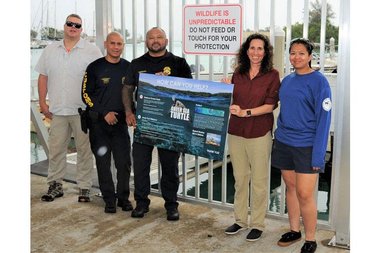National Oceanic and Atmospheric Administration Special Agent Charles Raterman, Guam Customs Officer Ike Reyes, NOAA Enforcement Officer John Evangelista, former Naval Facilities Engineering Command Marianas Natural Resources Specialist Tammy Summers and Guam Division of Aquatic and Wildlife Resources Biologist C.J. Cayanan display some of the messaging used to educate the public.