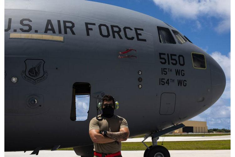 U.S. Air Force Staff Sgt. Tyler Garcia, 734 Air Mobility Squadron electrical and environmental systems craftsman, poses for a photo in front of a C-17 Globemaster assigned to the 154th Wing, Hawaii Air National Guard, after a Joint Forcible Entry Operation (JFEO) jump into Andersen Air Force Base, Guam, June 30. (U.S. Air Force photo by Senior Airman Michael S. Murphy)