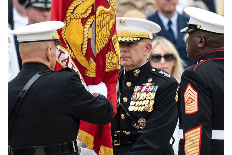 Retiring United States Marine Corps Commandant Gen. Robert Neller, left, presents the Marine colors to Gen. David Berger, who became the 38th Commandant of the Corps during a passage of command ceremony at Marine Barracks Washington, D.C., July 11, 2019. At right is Sergeant Major of the Marine Corps Ronald L. Green (EMMA SWISLOW/STARS AND STRIPES)