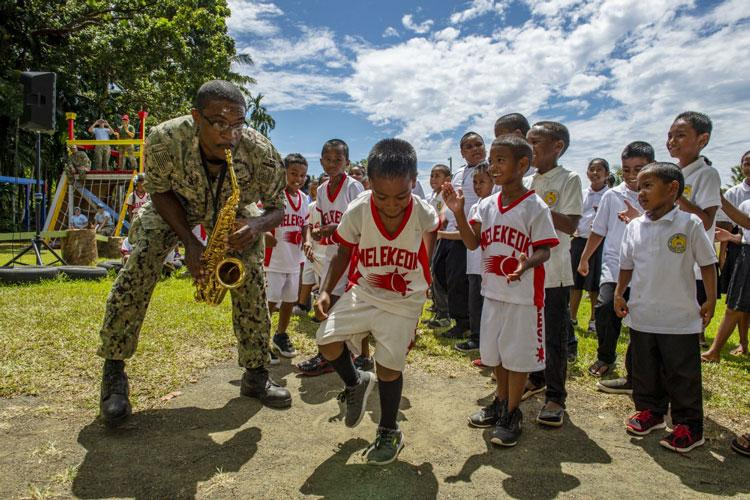 KOROR, Palau (August 13, 2019) Students at Melekeok Elementary School dance with Musician 3rd Class Jared Goodrum, a native of Albuquerque, N.M., during a concert by the U.S. 7th Fleet Far East Edition Brass Band during Civic Action Team (CAT) week. (U.S. Navy photo by Mass Communication Specialist 1st Class John Philip Wagner, Jr.)
