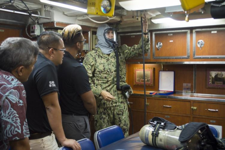 SANTA RITA, Guam (July 18, 2019) Lt. j.g. Brandon Conley, a native of Severn, Maryland, demonstrates how to use the Emergency Air Breathing (EAB) system to members of the Pacific Century Fellows Program-Marianas Chapter during a tour aboard USS Asheville (SSN 758), July 18. The purpose of the fellowship program is to develop potential leaders by creating leadership learning opportunities and experiences. (U.S. Navy photo by Lt. j.g. Meagan Morrison/Released)
