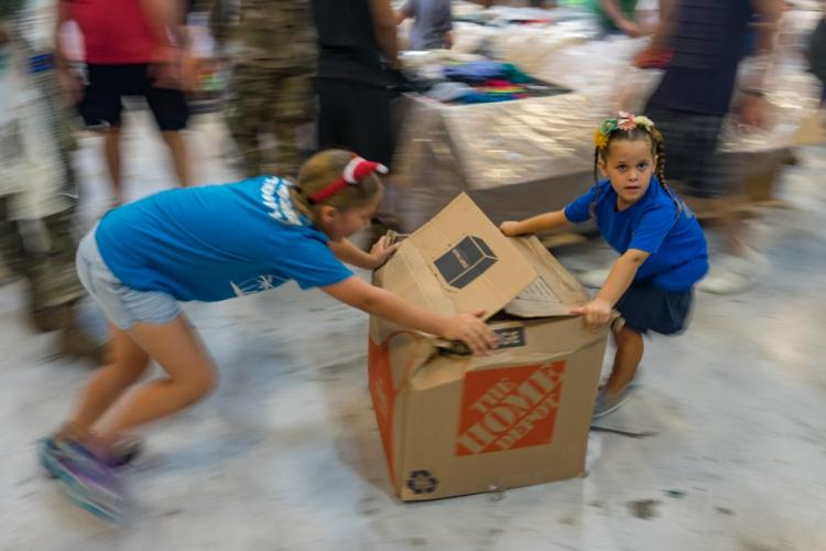 Volunteers slide a box of clothes to a supplies bundle at Andersen Air Force Base, Guam, Dec. 7, 2019. Operation Christmas Drop 2019 placed 176 bundles onto 56 Micronesian islands across the Pacific and the bundle build process is a family affair, with hundreds of volunteers showing up to help. (U.S. Air Force photo by Staff Sgt. Kyle Johnson)