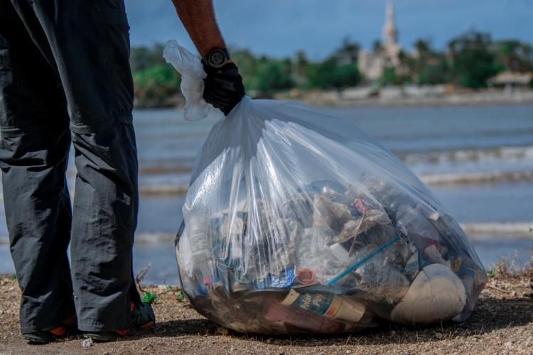 (INARAJAN, Guam) April 26, 2019 -- A Sailor grasps a bag of trash to be hauled away for proper disposal during a community relationship event in Inajaran for Earth Day. There were more than 40 volunteers whose efforts produced 50 bags of trash and multiple larger items such as tires, a payphone, pieces of metal, branches, and stone benches. (U.S. Navy photo by Mass Communication Specialist 1st Class Timmy Wakefield/Released)