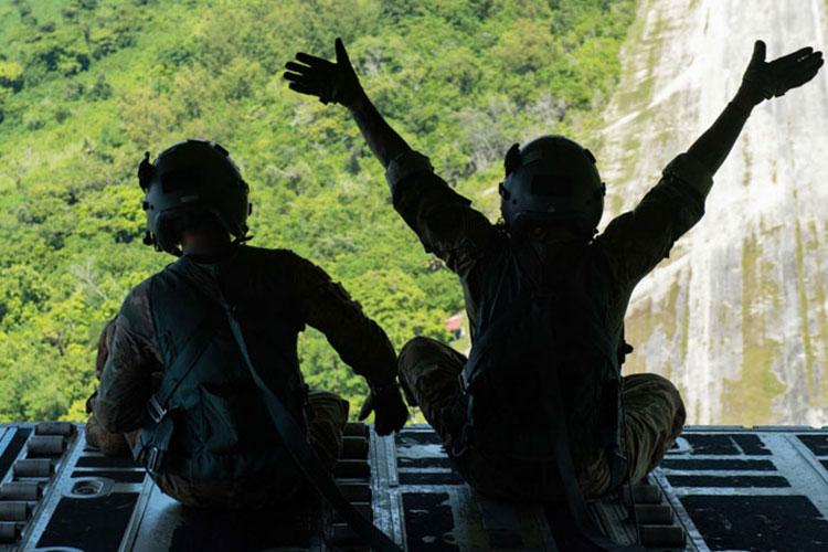 Staff Sgt. Hector Frietze, right, and Senior Airman John Allum, left, 36th Airlift Squadron loadmasters, wave to the people of the Island of Angaur, Republic of Palau, during the first bundle airdrops of Operation Christmas Drop 2020, Dec. 6. OCD is the world's longest running airdrop training mission, allowing the U.S. and its allies to deliver food, tools and clothing to the people who live on remote islands in the South-Eastern Pacific region. (U.S. Air Force photo by Staff Sgt. Gabrielle Spalding)