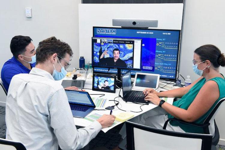 """A production team watches a broadcast of Dr. Neil deGrasse Tyson giving a keynote speech. Nearly 250 teams from 22 countries submitted proposals to take part in the """"Million Dollar International Quantum U Tech Accelerator"""" event in Rome, N.Y. This global engagement took place Sept. 1-3, and boasted cross-department support from the Air Force Office of Scientific Research and Office of Naval Research. (Courtesy photo)"""
