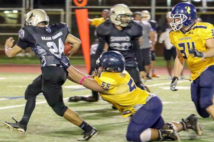 Guam High's Matua Whalen grabs a fistful of Simon Sanchez running back Erjan Sanchez's jersey. DONNA RHODES/SPECIAL TO STRIPES