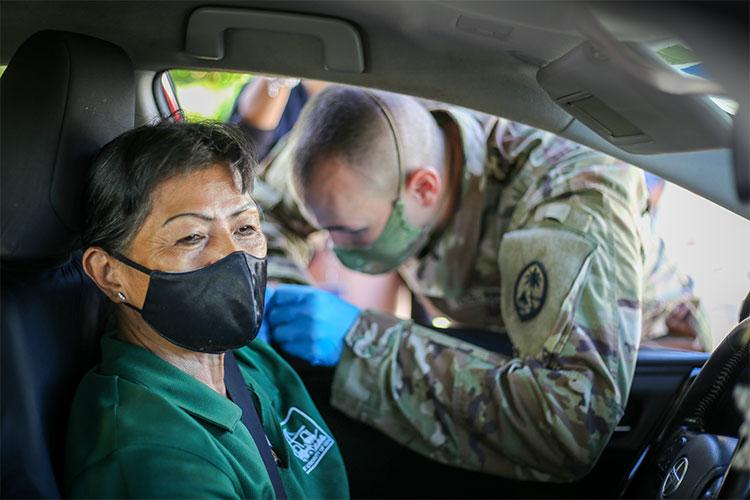 Spc. Michael Marsh of the Guam National Guard's Task Force Medical, right, administers a COVID-19 vaccination shot to a member of the community during a Strike Team community outreach point of distribution at the Port Authority of Guam in Piti on June 2, 2021.