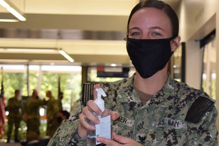 Navy Hospital Corpsman 3rd Class Mae Larimer, assigned to Navy Medicine Readiness Training Unit Bangor helps patients and visitors at the medical clinic to daily mitigate any potential spread of the ongoing pandemic outbreak as well as seasonal influenza virus. (Photo by Douglas Stutz.)