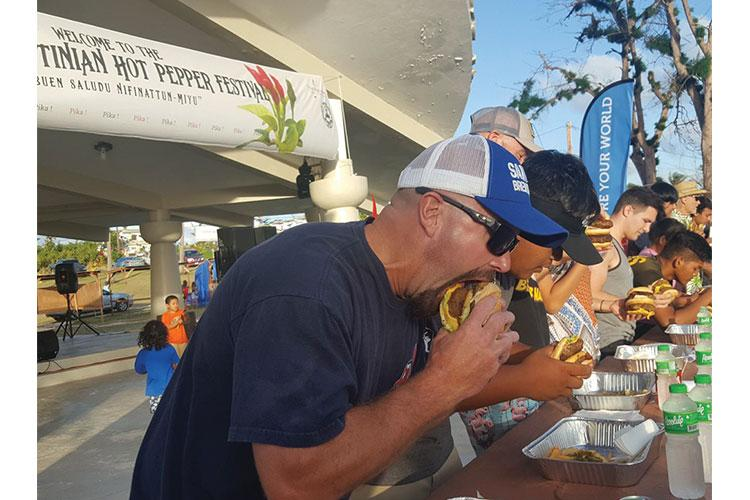 Competitors in the JC Café Pika Burger Eating Contest take their first bites at the 15th Annual Tinian Hot Pepper Festival on Feb. 16, 2019.