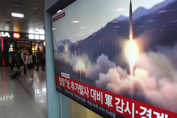 """A TV screen shows a file footage of North Korea's missile launch during a news program at the Seoul Railway Station in Seoul, South Korea, Saturday, May 4, 2019. The signs read: """"Strengthening military alertness."""" AHN YOUNG-JOON/AP"""