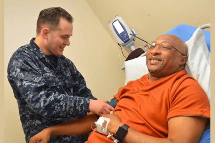 """Hospitalman Payton Dupuis, a native of Mill City, Oregon, checks veteran Joseph Levette's blood pressure at Naval Hospital Jacksonville's internal medicine clinic. """"Men's health is a vital part of the mission,"""" stated Dupuis. """"We need a healthy workforce to succeed."""" (U.S. Navy photo by Jacob Sippel)"""