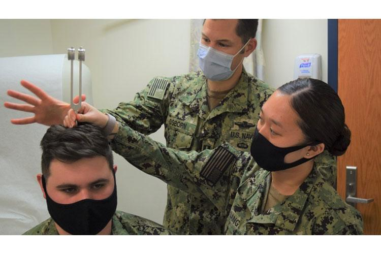"""Navy Lt. Jeffrey Osborn, physician assistant (PA) assigned to Navy Readiness and Training Command Bremerton's Branch Health Clinic Bangor demonstrates to Navy Hospitalmen Wendy Dang (right) and Nicholas Gevedon (seated) the Rinne and Weber test(s) routinely used to evaluate hearing loss. Osborn attests that """"the single best part of his job is training and working with corpsmen. (Photo by Douglas Stutz, NHB/NMRTC Bremerton.)"""