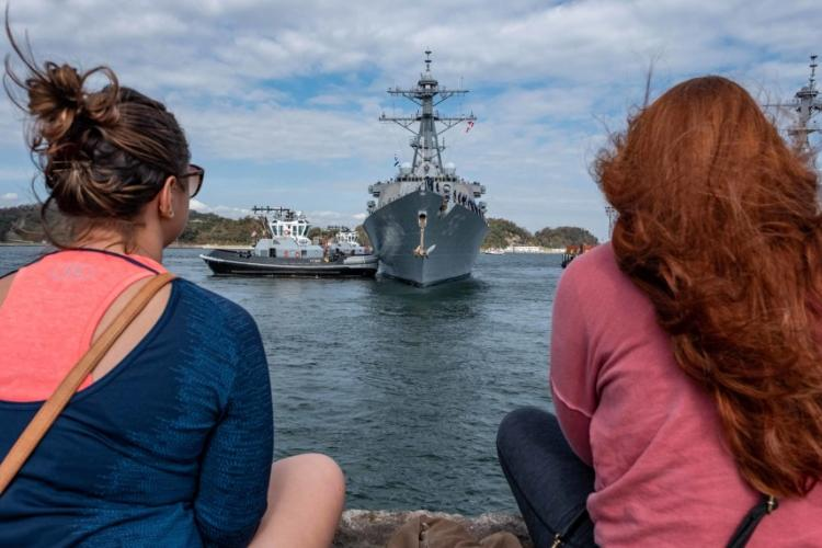Onlookers sit on a pier as the USS John S. McCain departs Yokosuka, Japan, Oct. 28, 2019, to conduct comprehensive at-sea testing, the ship's first underway since its collision in 2017. TORREY W. LEE/U.S. NAVY