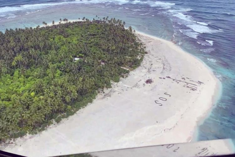An SOS in the sand can be seen in this screenshot taken from a DVIDS video. Guardsmen locate three missing mariners on Pikelot Island during a search and rescue mission in the Federated States of Micronesia southwest of Guam, Aug. 2, 2020. U.S. AIR FORCE